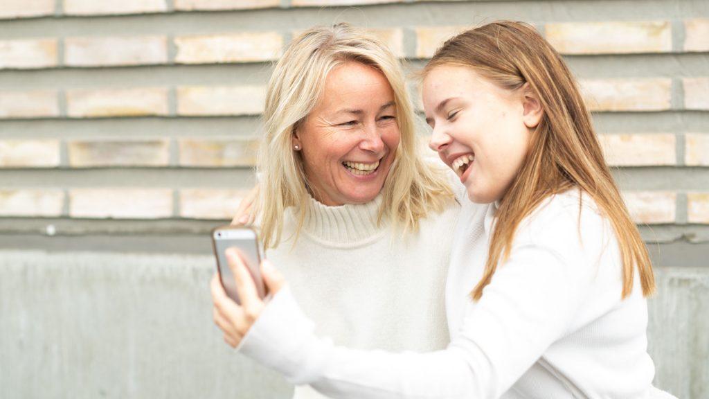 Kvinna och flicka, båda med vita tröjor, tar en bild tillsammans med en mobilkamera och skrattar.