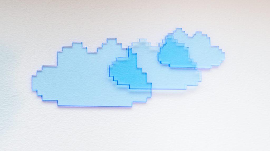Tre blå överlappande pixel-moln på vit yta.