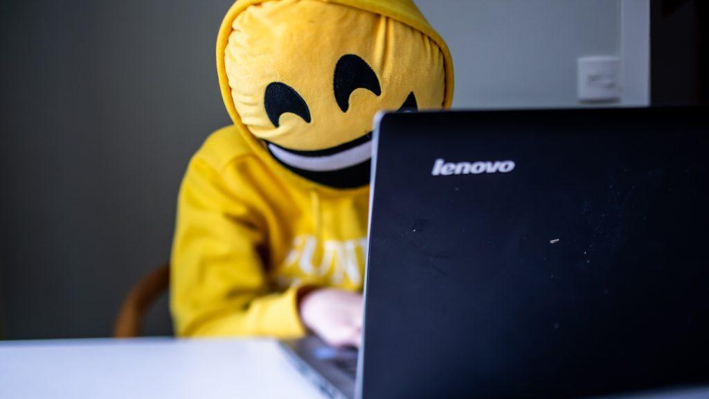 Person med smiley-kudde framför ansiktet och gul luvtröja använder dator vid skrivbord.