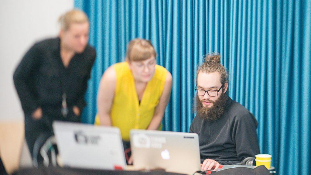 Person som använder en dator, medan två andra personer tittar på.