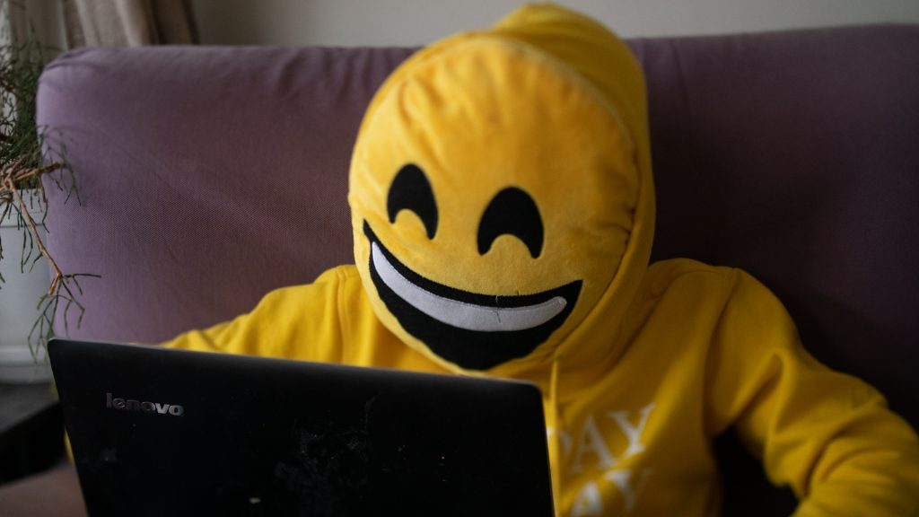 Person med smiley-kudde framför ansiktet och gul luvtröja använder dator i soffa.