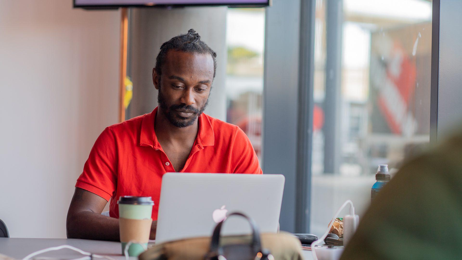 En man sitter i ett coworkingspace med en bärbar dator och en takeawaymugg kaffe