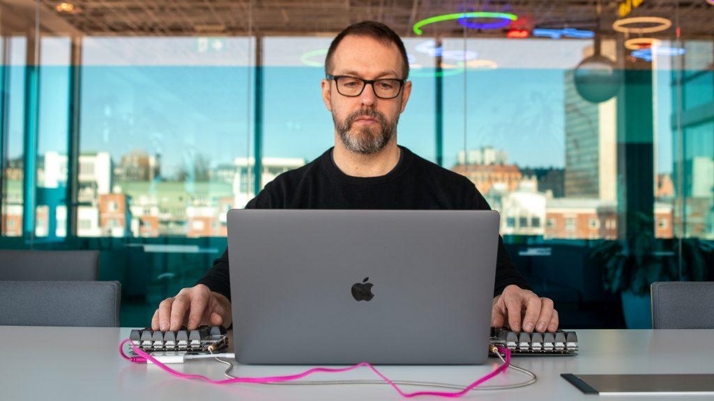 En man sitter vid en dator med ett mindre tangentbord på varje sida och jobbar med DNS
