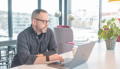 En man jobbar på en bärbar dator stående vid ett bord bredvid en krukväxt