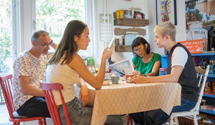 Familj som sitter runt frukostbordet, med tidning och mobiltelefon.